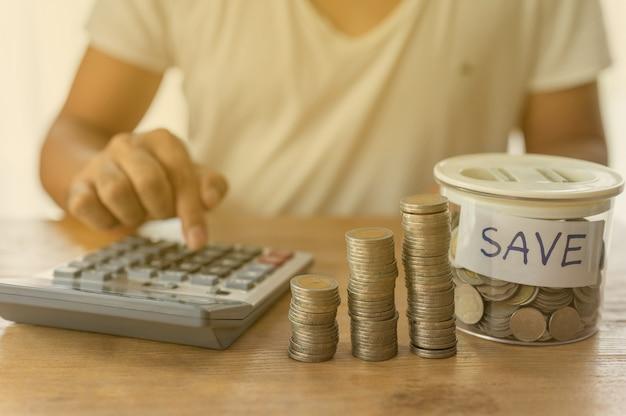 Der geschäftsmann verwendet einen rechner mit münzen, die sich in einer spalte ansammeln, die geldspar- oder finanzplanungsideen für die wirtschaft darstellen.