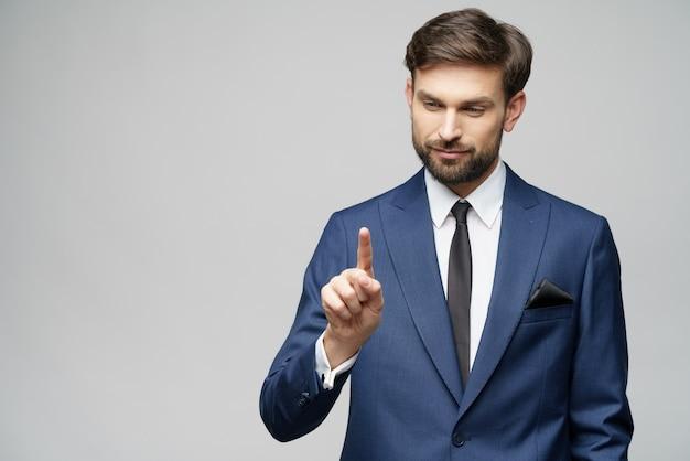 Der geschäftsmann zeigt mit dem finger auf den unsichtbaren bildschirm und drückt den digitalen virtuellen knopf über der grauen wand