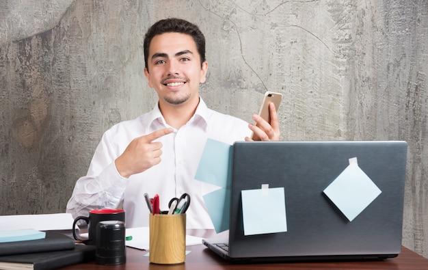 Der geschäftsmann zeigte glücklich mit seinem telefon auf den schreibtisch.