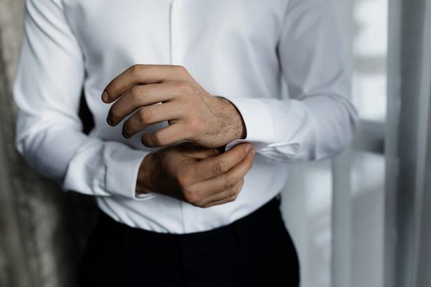Der geschäftsmann zieht das weiße hemd an, bereitet sich auf ein treffen vor