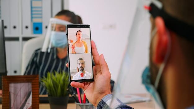 Der geschäftsmannführer führt die fernkommunikation mit smartphone für videomeetings und spricht mit remote-mitarbeitern, die im neuen normalen bürogebäude sitzen freiberufler respektiert soziale distanz