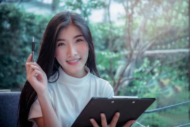 Der geschäftsstil des asiatischen grils hält einen stift und eine lächelnde emotionale positive sache des tages