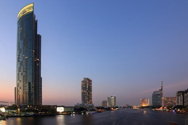 Der geschäftswolkenkratzer auf satorn-straße in der stadt im stadtzentrum gelegen zur sonnenuntergangzeit.
