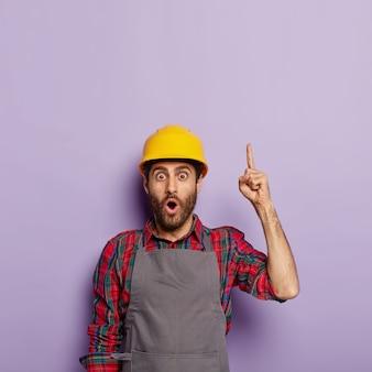 Der geschockte industriearbeiter trägt einen gelben helm und eine schürze