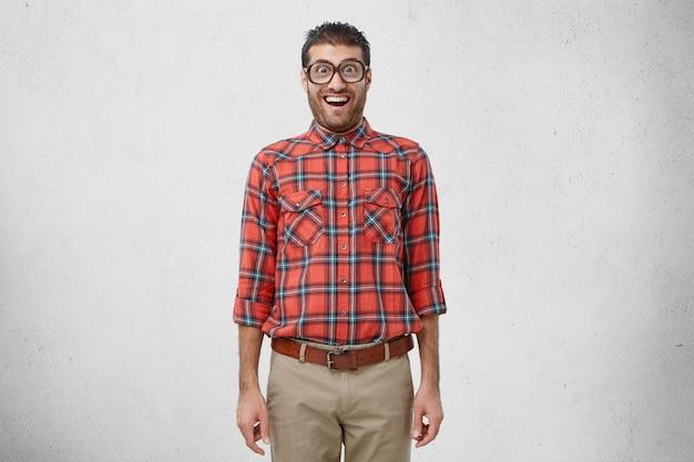 Der geschockte junge männliche nerd trägt eine alte modische brille, ein kariertes hemd und eine hose