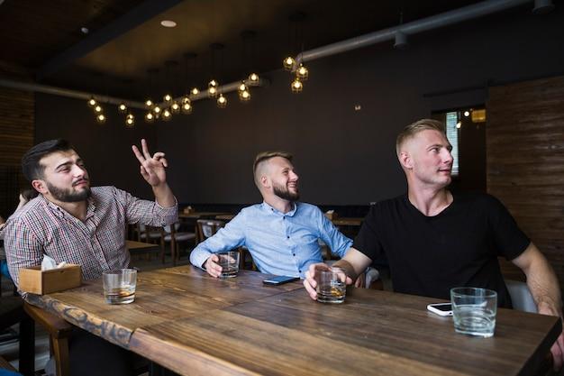 Der gestikulierende mann beim trinken dinks mit seinen freunden in der bar