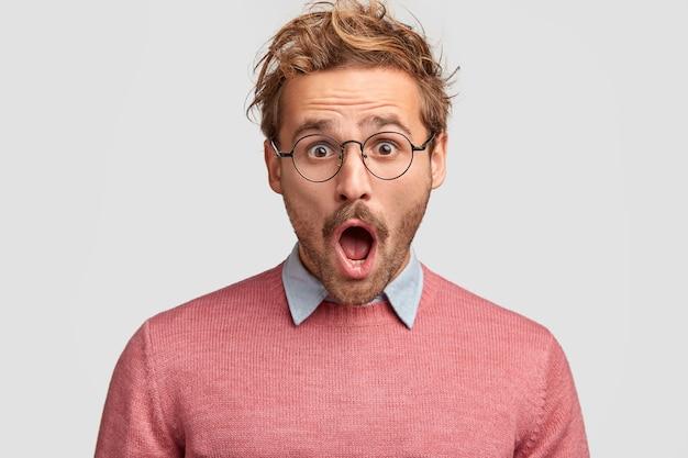 Der gestresste hipster-mann hat einen schockierten gesichtsausdruck, stellt fest, dass sein auto gestohlen wurde, hält den mund weit offen und starrt durch runde brillen