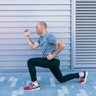 Der gesunde männliche läufer, der die übung ausdehnt, bevor er anfing zu laufen
