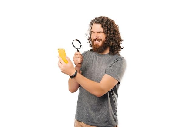 Der gewellte hipster-mann schaut durch eine lupe auf ein telefon.