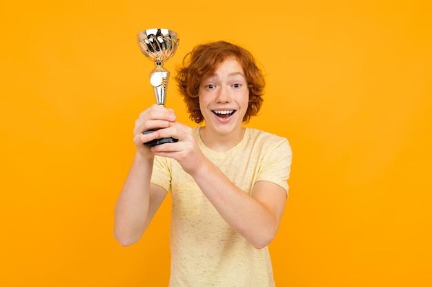 Der gewinner hält eine goldene tasse auf einem gelben hintergrund mit kopienraum