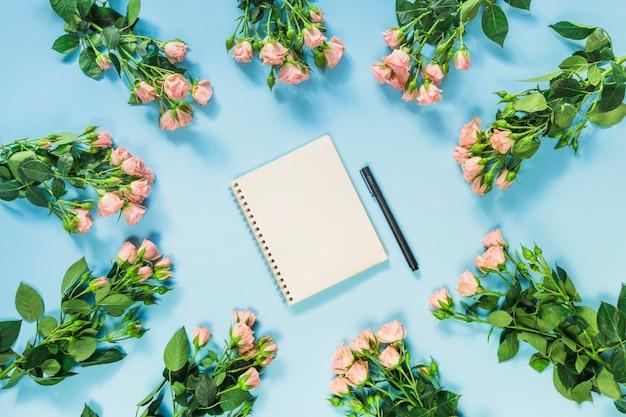 Der gewundene notizblock und der stift, die mit frischen rosen umgeben werden, blüht auf blauem hintergrund