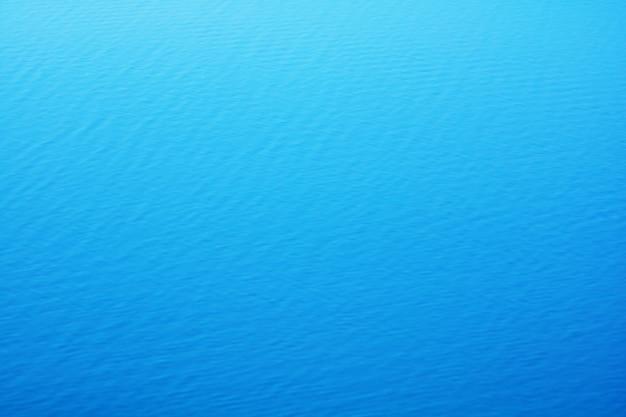 Der glatte natürliche hintergrund des blauen wassers mit bokeh