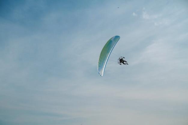 Der gleitschirm fliegt über den strahlend blauen himmel