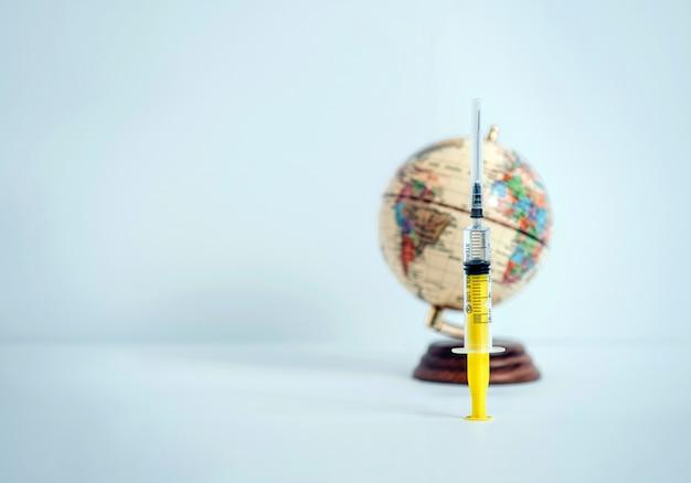 Der globus und die spritze auf einem blauen hintergrund.