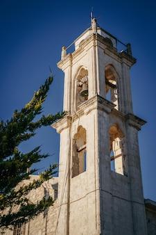 Der glockenturm der alten kirche gegen den blauen himmel