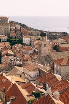 Der glockenturm des franziskanerklosters in dubrovnik vor dem hintergrund der dächer der