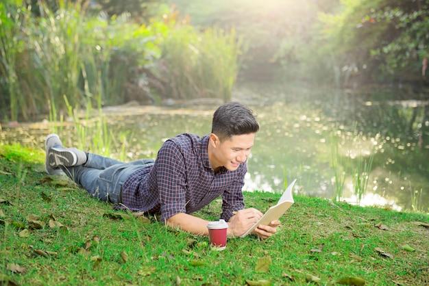 Der glückliche asiatische mann, der auf dem gras liegt und schreiben etwas auf das buch