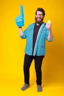 Der glückliche bärtige hipster hält sein handy in der hand und trägt einen fächerschaumhandschuh