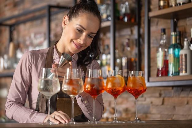 Der glückliche barkeeper macht einen aperol-spritz-cocktail an einer bar in fünf gläsern.