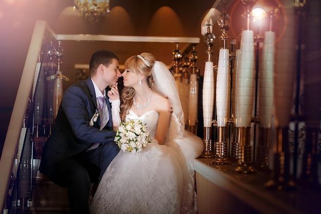 Der glückliche bräutigam und die braut sitzen auf einer treppe in der hotelhalle