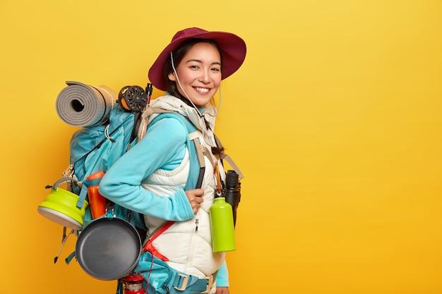 Der glückliche brünette asiatische reisende trägt einen großen touristenrucksack, benutzt ein fernglas für die reise, steht an der gelben wand, trägt einen eleganten hut und einen pullover mit weste