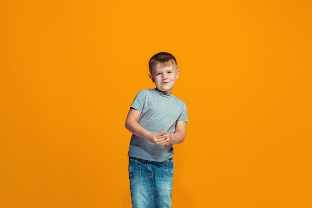 Der glückliche jugendlich junge, der gegen orange hintergrund steht und lächelt.