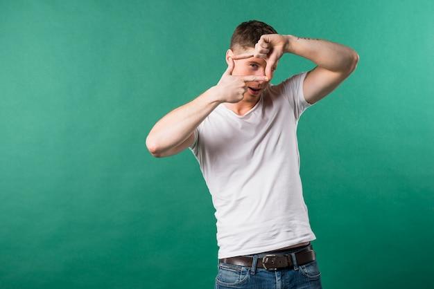 Der glückliche junge mann, der durch einen rahmen schaut, bildete sich durch seine hände gegen grünen hintergrund