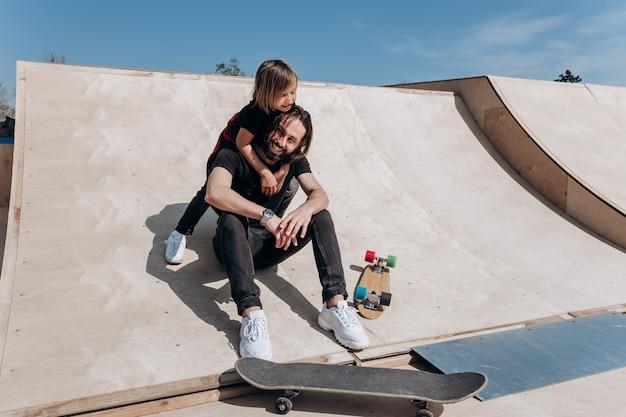 Der glückliche junge vater und sein sohn in der stylischen freizeitkleidung sitzen am sonnigen warmen tag in einer umarmung zusammen auf der rutsche neben den skateboards in einem skatepark.