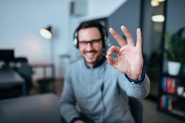 Der glückliche männliche kundendienstbetreiber, der okay zeigt, unterzeichnen herein sein büro.