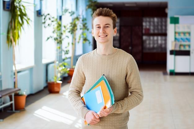 Der glückliche männliche student, der im campus am sonnigen tag hält bücher, übungsbücher steht, glücklich, in der universität zu studieren und hohe akademische leistung zu haben