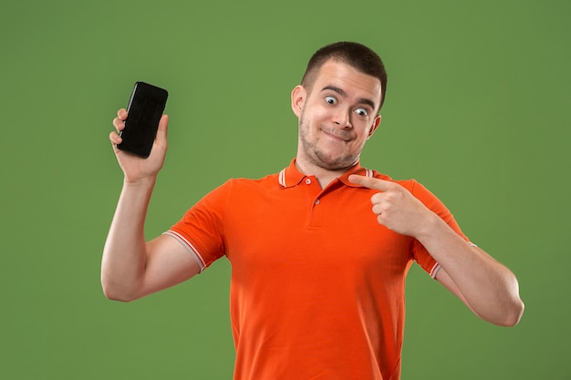 Der glückliche mann, der am leeren bildschirm des handys gegen grüne wand zeigt