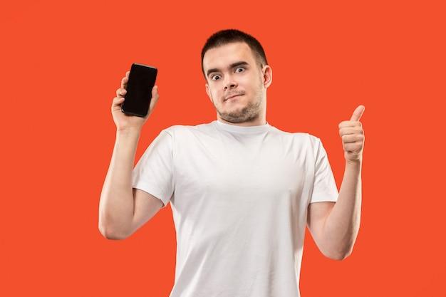 Der glückliche mann, der am leeren bildschirm des handys gegen orange hintergrund zeigt.