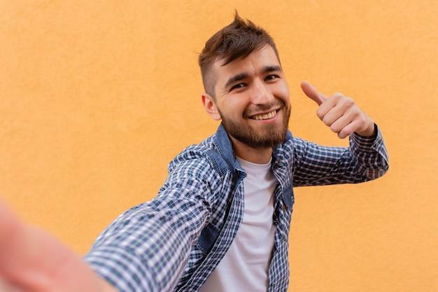 Der glückliche mann macht eine handbewegung vor dem hintergrund einer orangefarbenen wand