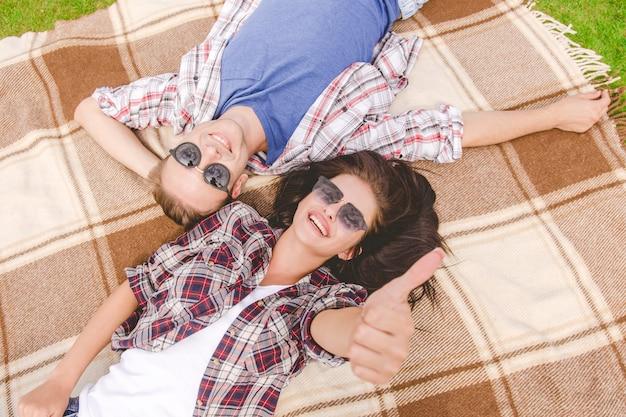Der glückliche mann und die frau mit sonnenbrille liegen und gestikulieren auf dem boden