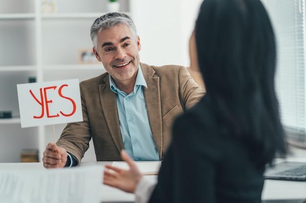 Der glückliche mann und die glückliche frau interviewen im büro
