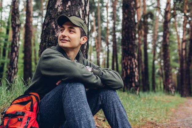 Der glückliche manntourist, der im frühjahr waldreisenden stillsteht, stoppte, um sich das kampieren zu entspannen und reiste