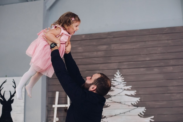 Der glückliche papa hält seine tochter in den armen und wirbelt mit ihr herum