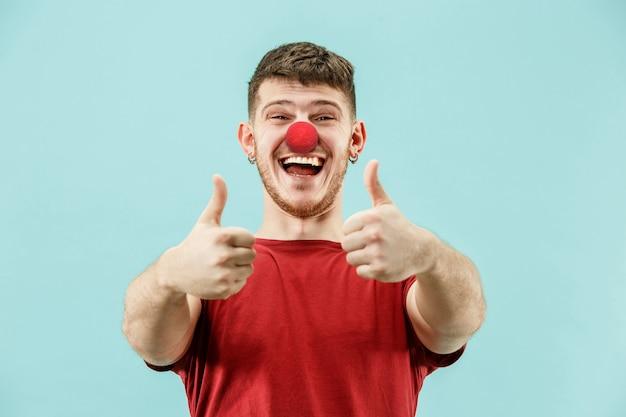 Der glückliche überraschte und lächelnde mann am tag der roten nase der clown, spaß, party, feier, lustig, freude, urlaub, humorkonzept