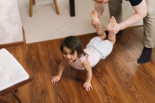 Der glückliche vater spielt mit dem kind, das seine tochterbeine hält, die auf dem boden krabbeln