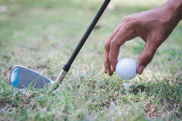 Der golfspieler, der mit einem golfschläger einen golfball auf den abschlag legt