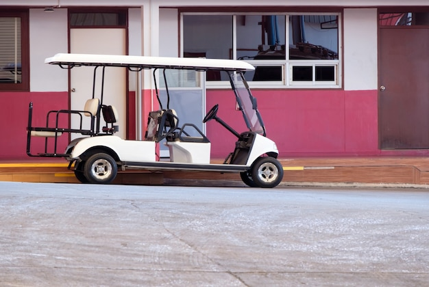 Der golfwagen wird in der nähe des büroteils für das ladegerät geparkt, bevor er durch die große fabrik patrouilliert, seitenansicht für den kopierraum.