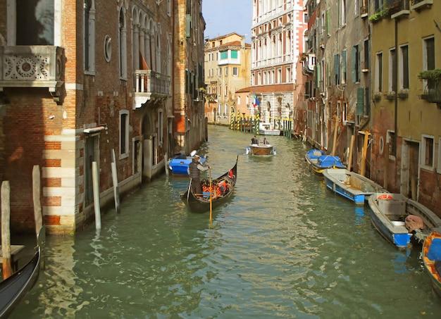 Der gondoliere, der eine gondel auf einem kleinen kanal von venedig, italien segelt