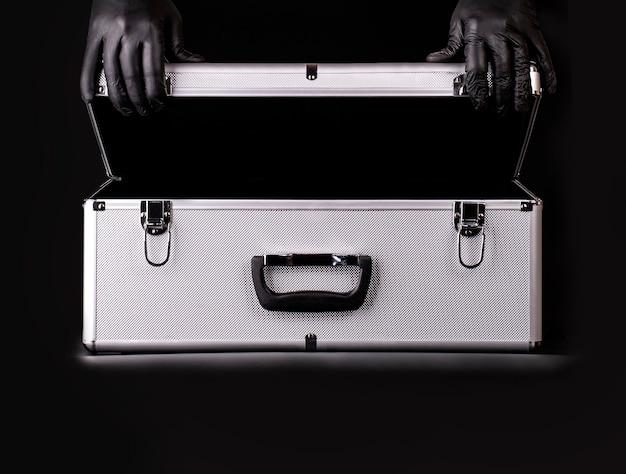 Der große aluminiumkoffer und die hände schwarzer sicherheitshandschuhe