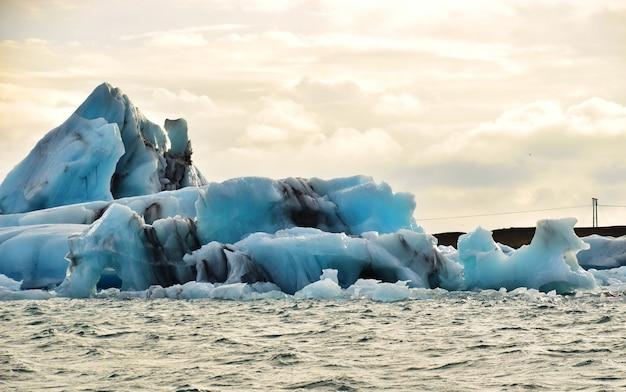 Der große blaue eisberg vom geschmolzenen gletscher, der in den ozean bei jokulsarlon, island schwimmt.