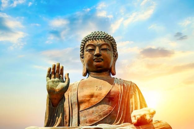 Der große tian tan buddha am po lin kloster in hong kong während des sonnenuntergangs.