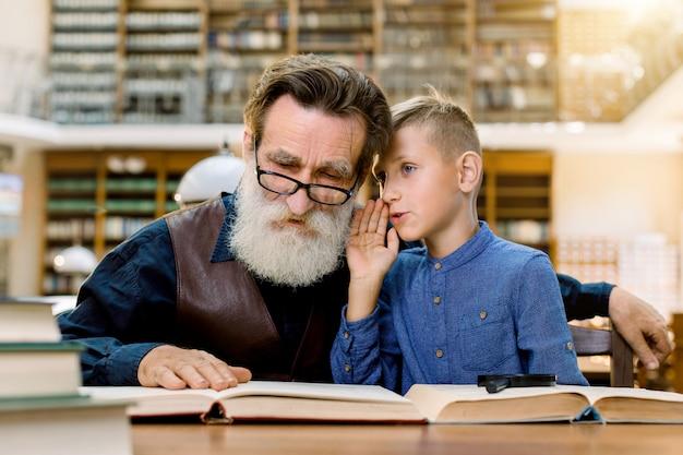 Der großvater eines älteren mannes und sein enkel lesen gemeinsam ein buch, während sie in der bibliothek auf dem hintergrund der vintage-bücherregale sitzen. glücklicher junge, der opa flüstert, familienlesung