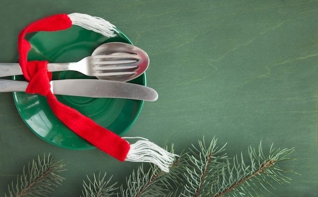 Der grüne teller und das besteck sind mit einem roten schal gebunden, auf grünem grund mit einem fichtenzweig, als menügestaltungselement