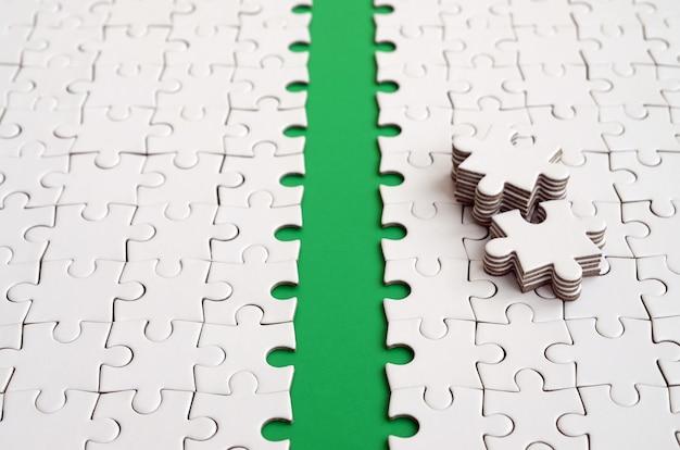 Der grüne weg wird auf die plattform eines weißen gefalteten puzzles gelegt