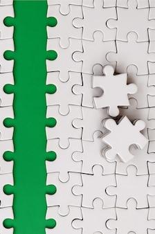 Der grüne weg wird auf die plattform eines weißen gefalteten puzzles gelegt.