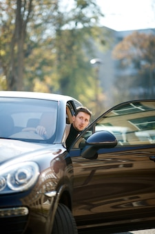 Der gut aussehende kaukasische fahrer schaut an einem schönen sonnigen tag von der geöffneten autotür auf der stadtstraße